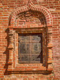 Fragment of a brick wall with a window. Fragment of an ancient brick wall with closed window Stock Photos