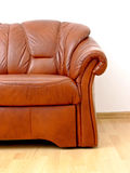 Fragment of brown sofa. Fragment of comfortable brown leather sofa on wooden floor near white wall Stock Photography