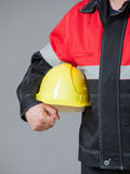 Fragment of a builder holding yellow hard hat Royalty Free Stock Photos