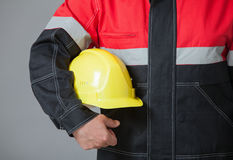 Fragment of a builder holding yellow hard hat Stock Photography