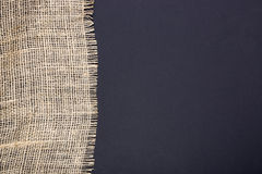 Fragment of burlap on black Stock Photography