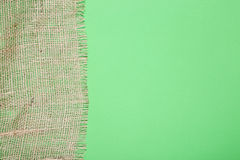 Fragment of burlap on green Stock Images
