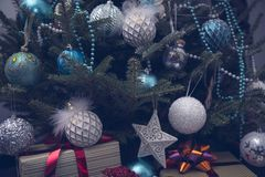 A fragment of a Christmas tree with baubles and gifts stock image