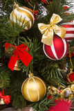 Fragment of Christmas tree decorated. Fragment of Christmas tree with baubles, balls and bows ornaments and gifts. A lovely traditional Christmas tree decorated Stock Photo