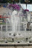 Fragment of a city fountain with splashes and water on a sunny day Royalty Free Stock Image