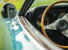 Classic car. Fragment of a classic car showing rear view mirror on the side and dash board with steering wheel Stock Photography