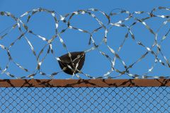 A fragment of clothes on the fence with barbed wire. stock image