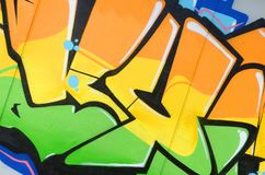 Fragment of colored street art graffiti paintings with contours and shading close up. Background texture of youth contemporary art culture. Orange yellow and stock image