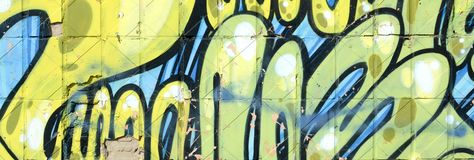 Fragment of colored street art graffiti paintings with contours and shading close up. Background texture of youth contemporary art culture. Green yellow colors stock image