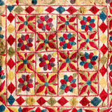 Fragment of colorful retro tapestry textile pattern with handmade floral ornament as background. royalty free stock images