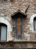 Fragment d'un mur d'un vieux bâtiment avec un moine tenant la paix de mot et bon à Assisi Photos libres de droits