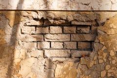 Fragment d'un mur de briques avec le plâtre effondré Photos stock