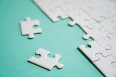 Fragment d'un puzzle denteux blanc plié et une pile des éléments mal peignés de puzzle dans la perspective d'une surface colorée photos libres de droits