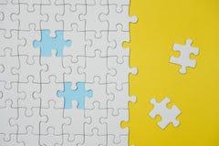 Fragment d'un puzzle denteux blanc plié et une pile des éléments mal peignés de puzzle dans la perspective d'une surface jaune photos libres de droits