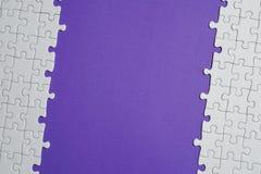 Fragment d'un puzzle denteux blanc plié et une pile des éléments mal peignés de puzzle dans la perspective d'une surface violette photographie stock libre de droits