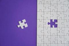Fragment d'un puzzle denteux blanc plié et une pile des éléments mal peignés de puzzle dans la perspective d'une surface violette photo libre de droits