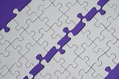 Fragment d'un puzzle denteux blanc plié et une pile des éléments mal peignés de puzzle dans la perspective d'une surface violette images stock