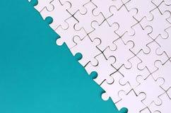 Fragment d'un puzzle denteux blanc plié sur le fond d'une surface en plastique bleue Photo de texture avec l'espace de copie pour photographie stock libre de droits