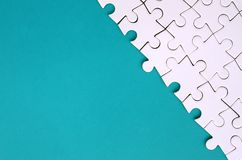 Fragment d'un puzzle denteux blanc plié sur le fond d'une surface en plastique bleue Photo de texture avec l'espace de copie pour images libres de droits