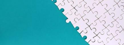 Fragment d'un puzzle denteux blanc plié sur le fond d'une surface en plastique bleue Photo de texture avec l'espace de copie pour photographie stock