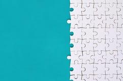 Fragment d'un puzzle denteux blanc plié sur le fond d'une surface en plastique bleue Photo de texture avec l'espace de copie pour photos libres de droits