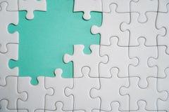 Fragment d'un puzzle denteux blanc pli? et une pile des ?l?ments mal peign?s de puzzle dans la perspective d'une surface color?e images libres de droits