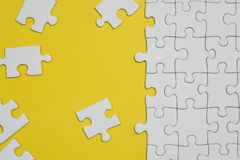 Fragment d'un puzzle denteux blanc pli? et une pile des ?l?ments mal peign?s de puzzle dans la perspective d'une surface jaune images libres de droits