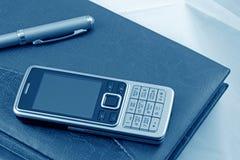 Fragment de l'agenda, du téléphone portable et du crayon lecteur (bleus) Images stock