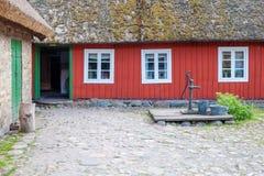 Fragment de maison de village et de pompe à eau Photographie stock