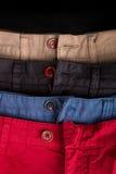 Fragment de quatre pantalons de sergé de coton rouges, bleu, noir, beige avec les boutons ouverts Fin vers le haut Photographie stock libre de droits