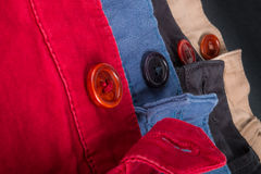 Fragment de quatre pantalons de sergé de coton rouges, bleu, noir, beige avec les boutons ouverts Fin vers le haut Image stock
