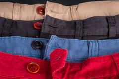 Fragment de quatre pantalons de sergé de coton rouges, bleu, noir, beige avec les boutons ouverts Fin vers le haut Image libre de droits