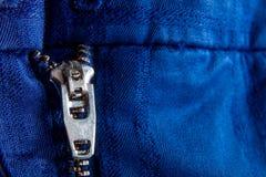 Fragment de veste bleue avec la tirette en métal fond zip-lock Fin vers le haut Photos libres de droits