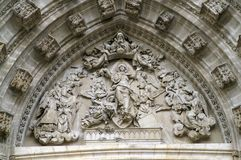 Fragment of the decoration of the cathedral. Detail of the arch of the Catholic Cathedral in Seville Spain. Stone carving. Sculptures in the arch of the Gothic Stock Photo
