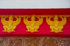 A fragment of decoration, Golden creature on a red background. Nakhon Ratchasima. Thailand. Royalty Free Stock Images