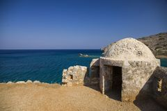Fragment of a defense tower and walls in the Spinalonga fortress. Sea view from the leper island in Greece.  royalty free stock images