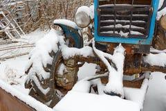 Fragment der Front eines alten Traktors bedeckt mit Schnee Stockfoto