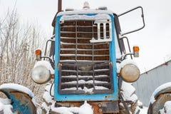 Fragment der Front eines alten Traktors bedeckt mit Schnee auf einem bewölkten Winterhimmel des Hintergrundes Stockfotos
