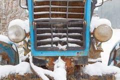 Fragment der Front eines alten Traktors bedeckt mit Schneenahaufnahme Stockbild