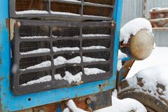 Fragment der Front eines alten Traktors bedeckt mit Schneenahaufnahme Stockfotografie
