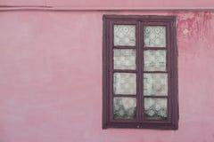 Fragment der Seitenwand mit altem Fenster und einem Gasrohr über ihm Lizenzfreies Stockfoto