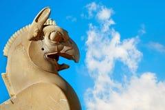Fragment der Steinsäuleskulptur eines Greifs in Persepolis gegen einen blauen Himmel mit Wolken Altes Achaemenid-Königreich iran Stockfotografie