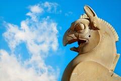 Fragment der Steinsäuleskulptur eines Greifs in Persepolis gegen einen blauen Himmel mit Wolken Altes Achaemenid-Königreich iran Stockfotos