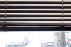 Fragment des abat-jour vénitiens blancs avec la corde d'ascenseur et la tige de rotation d'un contrôle manuel sur un premier plan Image libre de droits