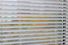 Fragment des abat-jour vénitiens blancs sur une fenêtre Photo stock