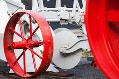 Fragment des alten Traktors mit roten Rädern Lizenzfreie Stockbilder