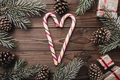 Fragment des Inneneinstiegs Tannenzweige, dekorative Kegel Bunte Süßigkeiten Geschenke für Weihnachten stockbild