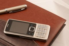 Fragment of diary, mobile phone and pen. On abstract gray background Stock Image