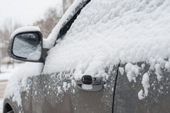 Fragment of a dirty car under a layer of snow during heavy snowfall, car is covered with snow, key inserted in the door stock photos