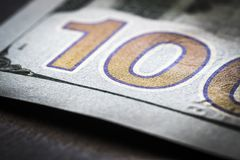 Fragment 100-dollar bill. A fragment of a 100-dollar bill on a black table close-up stock image